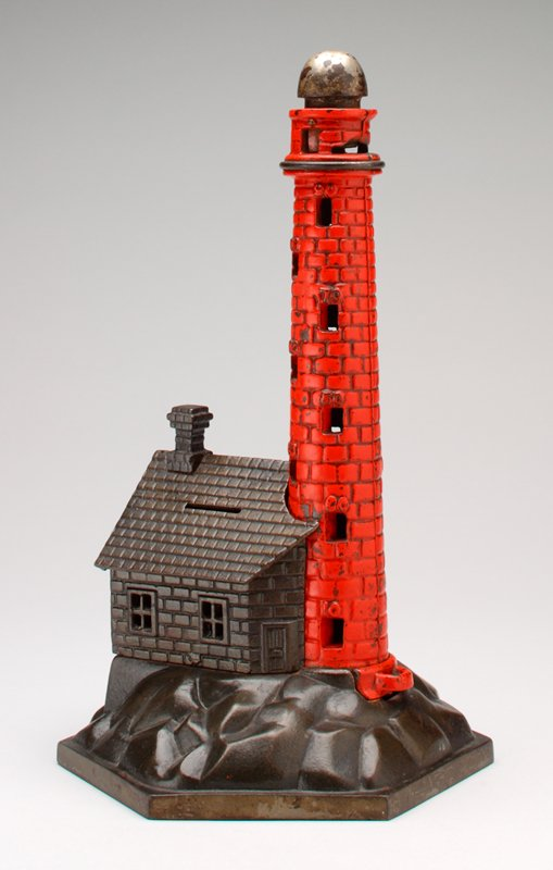 red brick lighthouse behind small building with sloping roof and small chimney; both of these buildings on a rocky platform