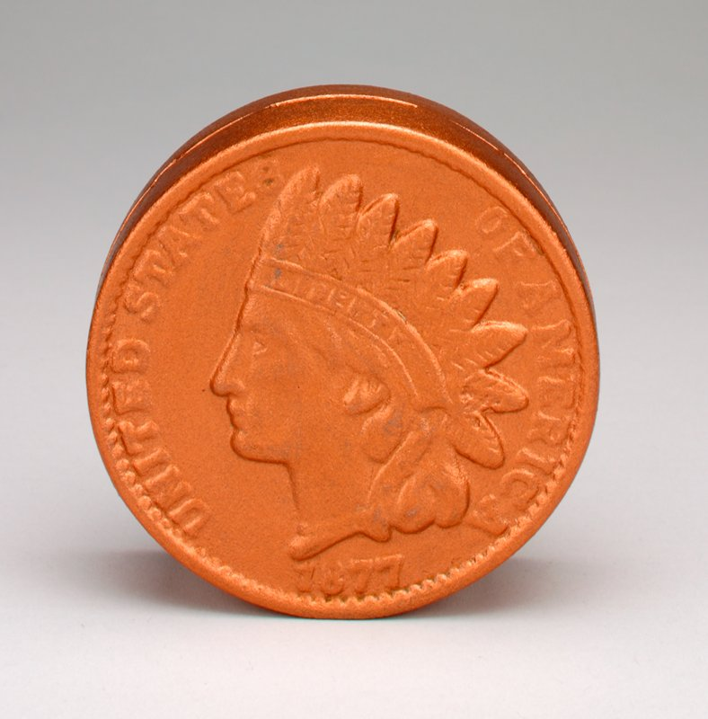 copper-painted metal in the shape of an 1877 penny; profile of man on one side; shield and wreath on opposite side