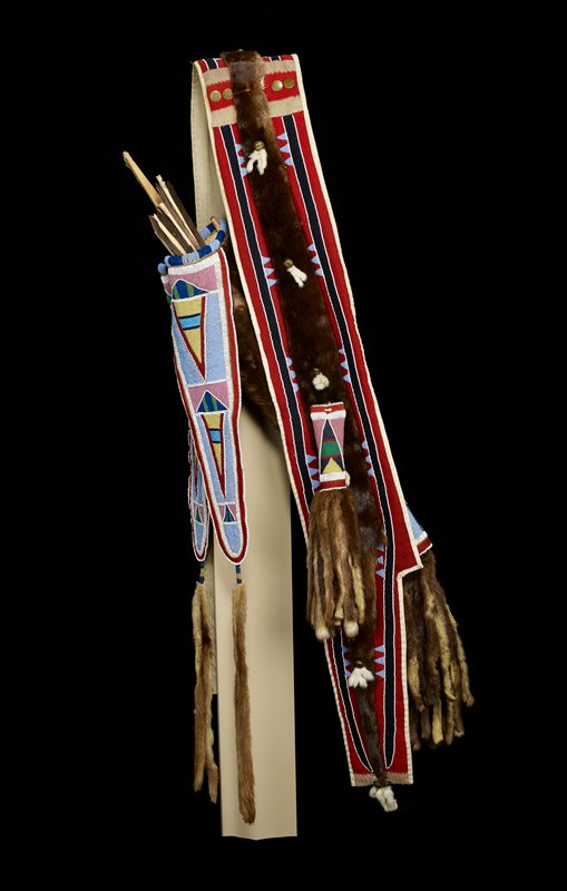 two otter hide tubes with hide tassels and long beaded and hide-detailed pendants; cross-body shoulder strap of red and blue felt with blue and white beads and bells; geometric beading in mostly triangular shapes