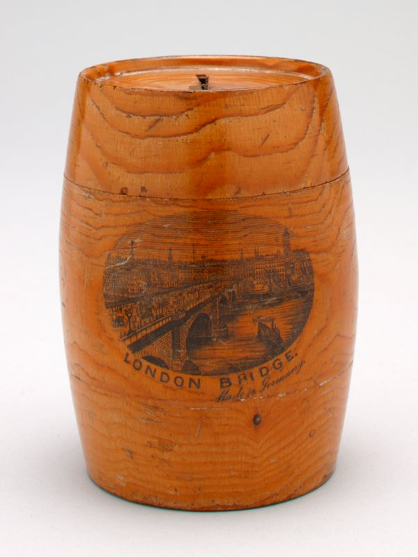 wood barrel-shaped bank; highly grained; pull-off top with coin slot; black transfer print on front with a view of London Bridge