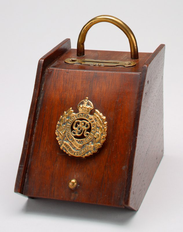 wood box bank with a dark finish; brass hanger on back; brass handle and brass embellished coin slot on top; brass Royal Engineers insignia and brass knob on the front