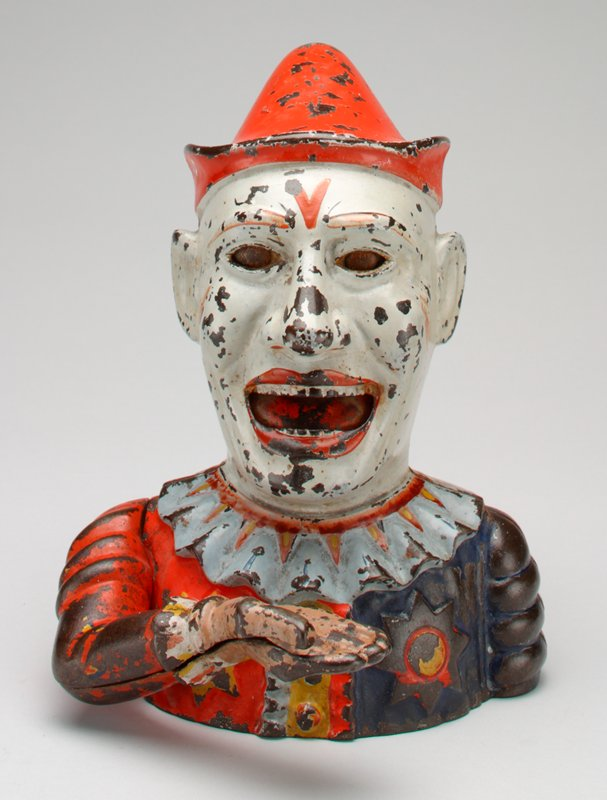 mechanical bank in the form of a clown with painted face wearing red peaked cap, red and blue suit with stars and grey ruffled collar