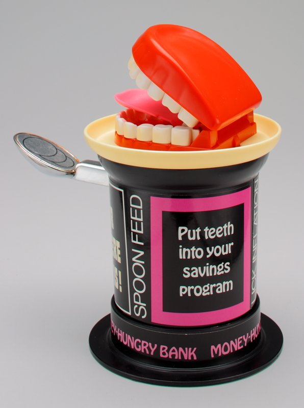 "black can with ""spoon"" sticking out of side and set of false teeth on top; place coin on spoon and press down; when spring releases, coin flips up, teeth open and coin lands on tongue; bottom of can turns and detaches"