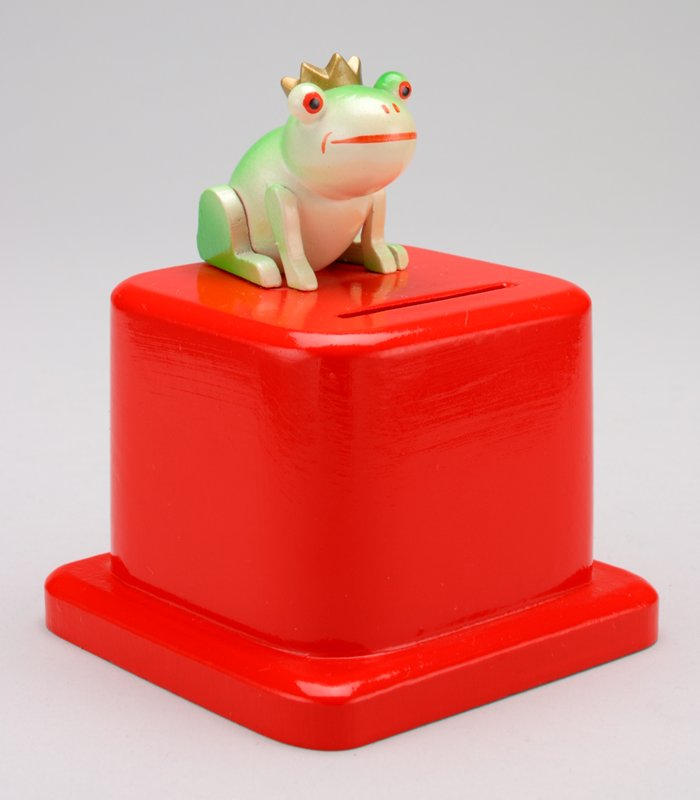 green frog wearing a crown seated on a much larger red footed square pedestal; key taped to door at underside; coin slot in front of frog in red square at top front