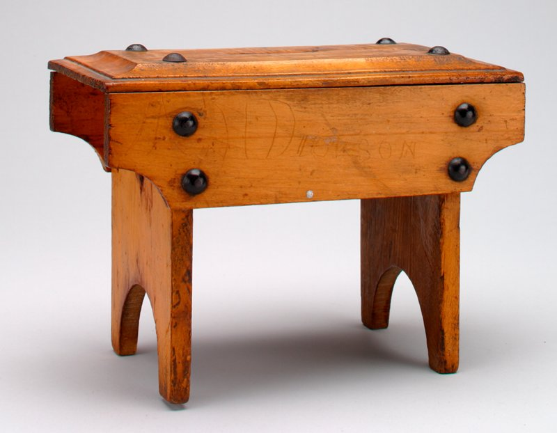 wooden miniature drop-leaf side table; leaves are built into sides; 4 round-head fasteners at top and both sides for decoration; 1/4 round raised top with coin slot at center