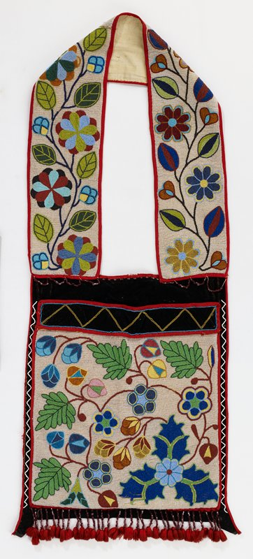 pouch and strap have clear beaded ground with organic floral designs; red beaded fringe with red wool tassels; black velvet and red knit trim