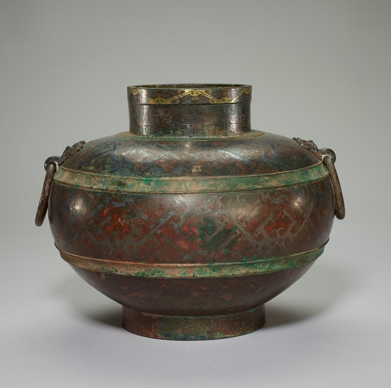 Wine vessel; bronze with gold, silver, and copper inlay. This vessel, variously called Hu, Lei, and Min is closely related to the Ting inlaid with silver, Karlgren Number 47 (50.46.76), and may possibly be part of the same set. The decor of the several belts is largely based on single and double volutes and volutes with triangles. These typical elements of the Huai decor must, to a degree, be extremely corrupted and geometricized derivatives of zoomorphic motifs (dragons and birds). The moveable ring handles, with an inlaid pattern, are fixed in the mouths of silver t'ao-t'ieh masks applied to the shoulder. The inlay in this decor belt includes gold as well as silver; the remainder is in silver only. This wine vessel is one of the most splendid examples of Late Chou bronze art and the inlay technique. Patina dark brown with green patches.