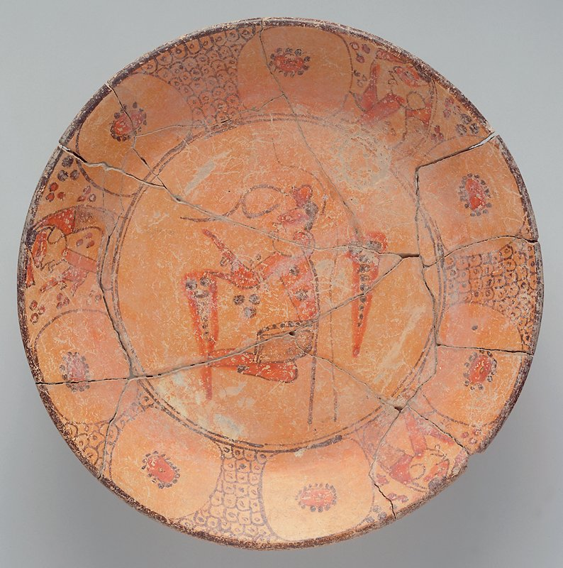 Plate with decoration in orange, red and brown; central male figure; rim with alternating designs of large circles with flower-like designs inside, concentric pairs of circles and figures. Completely broken and badly re-glued back together.
