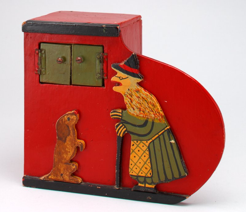 box bank with small shelf on side painted red and black with green doors and cut-out figures of a witch and a dog; brown dog is sitting up begging; witch has a can and is wearing a black hat, green dress, shawl and apron