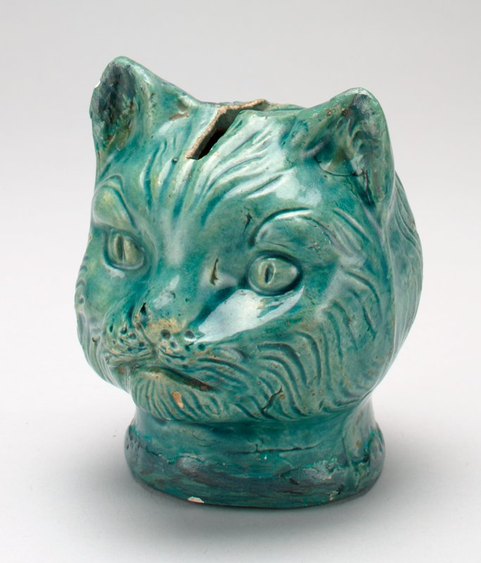 "turquoise ceramic cat head with shiny glaze; ""V. MASON"" stamped on bottom; coin slot on top of head"