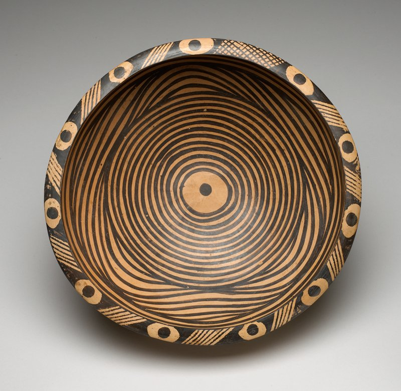 """thinly potted circular form with steeply rounded sides resting on flat rimless foot; painted black in linear design of concentric rings encircling round """"eye"""" in center with two bands of arcs around the well above and below a central divider of three horizontal lines; everted rim, decorated with multiple """"eyes"""" separated by clusters of oblique lines and one sector of crosshatched lines; exterior painted with three long wavy-line motifs, each ending with a curled-back hook and joining to form a continuous frieze below the rim; burnished overall to a smooth surface"""