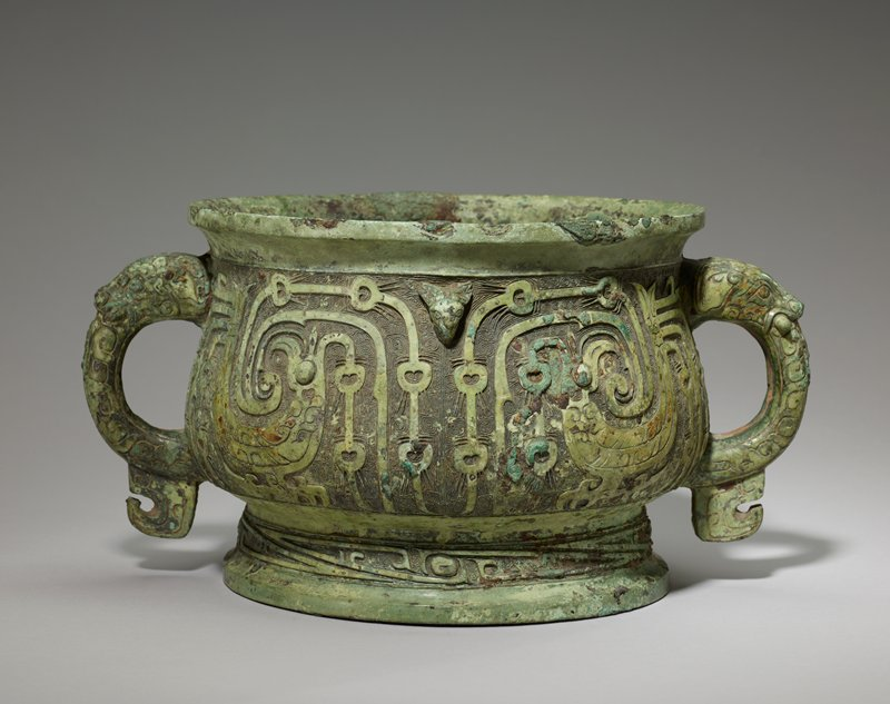 This unique vessel displays a technical perfection which proves that the artisans of Early Zhou sometimes fully equaled their Yin predecessors in taste and skill. The usual division into four panels is suggested exclusively by the free animals' heads alternating, in the neck region, with the handles. The decor ground, of rounded and acute angled spirals, carries an eyed band with diagonals in the foot belt and antithetical tail-raising birds in flat relief on the belly. The crests of these extraordinary birds split up in three strands, the middle one a short, spearlike point; the other two forming long plumes, one falling staight down past the turned head and in front of the breast, the other going forward past (and parallel with) the beak, then rising in a bold sweep above the head and descending in two parts behind the first strand. Thus three parallel bands descend, the outer two adorned with rounded figures reminiscent of those of a peacock. For comment of these figures see Karlgren, number 29, 50.46.120. From the raised tail three bands descend in a fashion exactly similar to those of the crest. The animal's head on the handle has large tusks protruding at the sides. The hook on the bottom is reminiscent of the bird representation often seen on Kuei handles. patina pale green with patches of blue green. The meaning of the inscription is ' The King attacked Tsi-yu and went out and attacked Naohei. When he came [back], he made liao-sacrifice [burnt-offering] in Tsung Chou and presented to [me], Kuo Po X, cowries, ten double strings. [I] presume in response to extol the king's grace, and so I have made my accomplished dead father's precious Kuei vessel. May for a myriad years sons and grandsons forever treasure and use it.' For comment on the inscription, see Karlgren, number 36 (50.46.119). The birds on the Kuei have a clase parallel on a 'YU' in the Simitomo Collection (Senoku, Volume 2, Plate 67) and on a 'TSUN' in the Imperial Collection, but are, for the rest