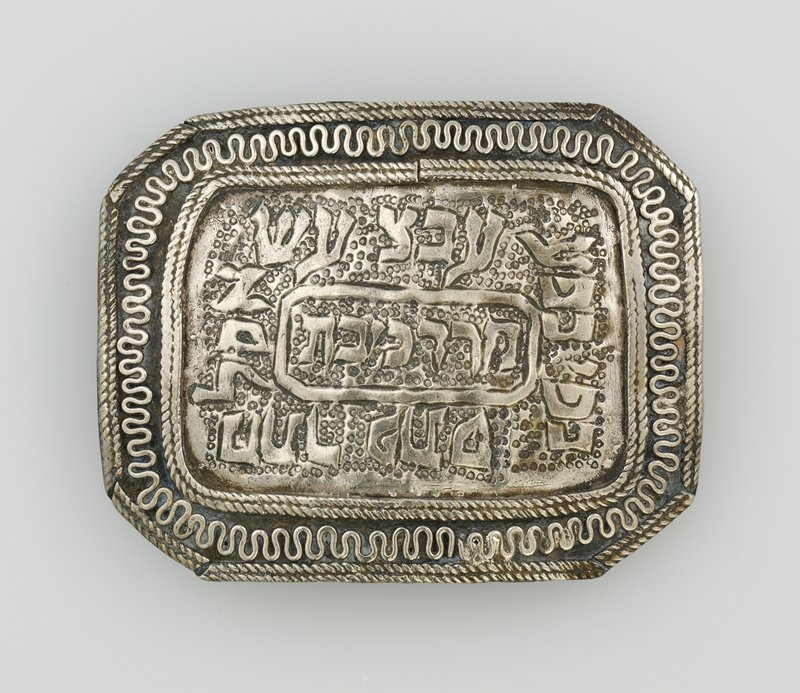 buckle with 4 loops on back; rectangular shape with squared-off corners; Hebrew text in relief at center; wavy wire border flanked by pairs of twisted wires