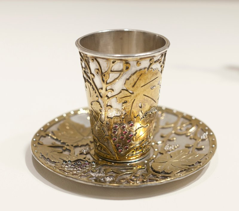 small tumbler-style cup; both cup and saucer are silver with overlay grape, vine and leaf design in brass with garnet grape accents