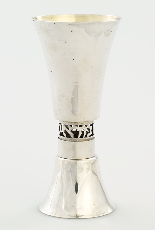 small cup on one end and larger cup on opposite end, gold-plated at interiors; silver movable ring covers one of 2 openwork rings of text between cups- ring falls when cup is turned over