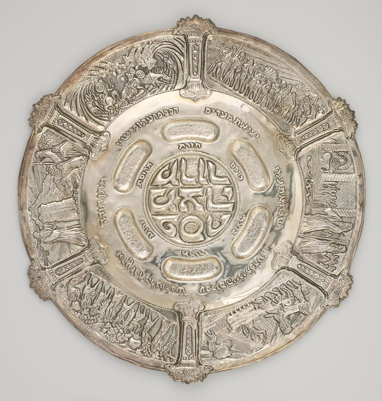 large platter; 6 wells around central circular depression; raised text in center area; scenes with figures around center