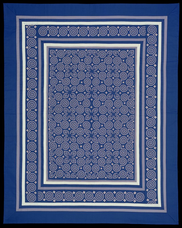 curvilinear central design of scrolls and leaflike shapes in applique and reverse applique with grey and blue fabric; white squares embroidered with blue and brown incorporated into design; scroll motif border; white backing