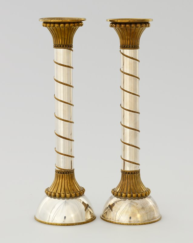 domed foot; tall shaft; silver patina on body with gold patina trim; gold spiral around shaft; relief buildings around candle cup