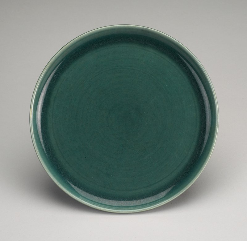 green plate with tall rim; raised foot