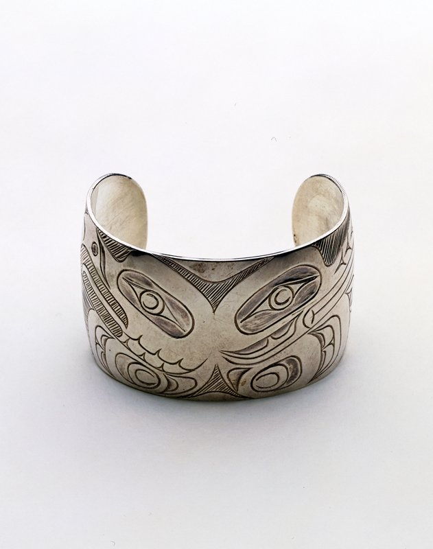 small c-shaped bracelet with incised decoration of 2 stylized birds' heads facing outward; one wing of each bird visible at outer edges
