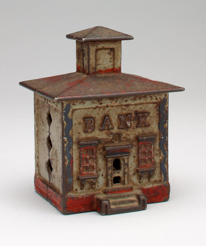 small building; door and 2 windows on front, coin slot in back; tower on roof; traces of red paint