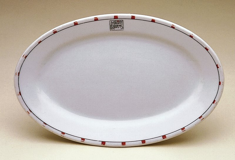 oval white porcelain body with trademark Frank Lloyd Wright red squares around the perimeter