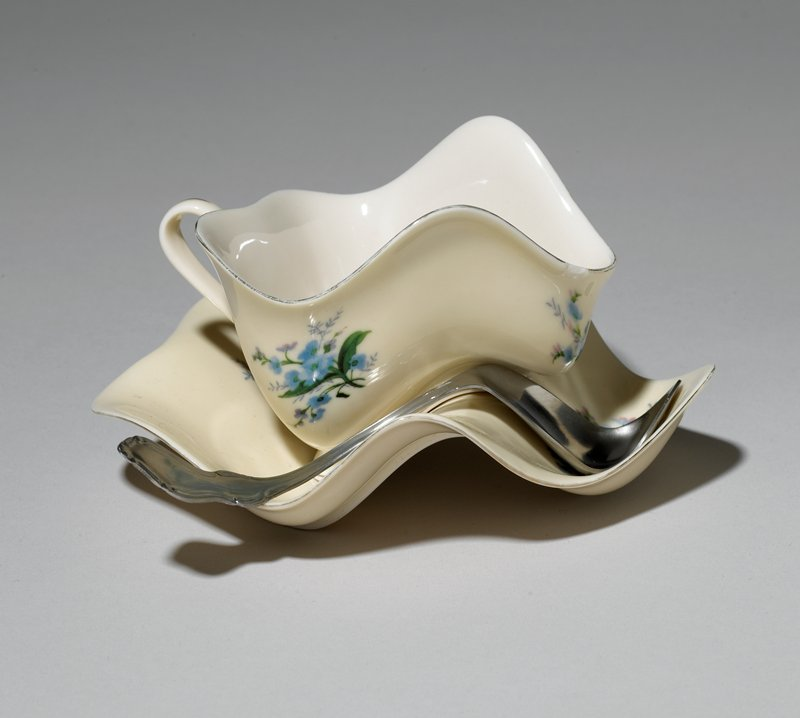 teacup and saucer decorated with blue flowers and silver trim, and distorted into undulating shapes; distorted spoon fits curves of saucer