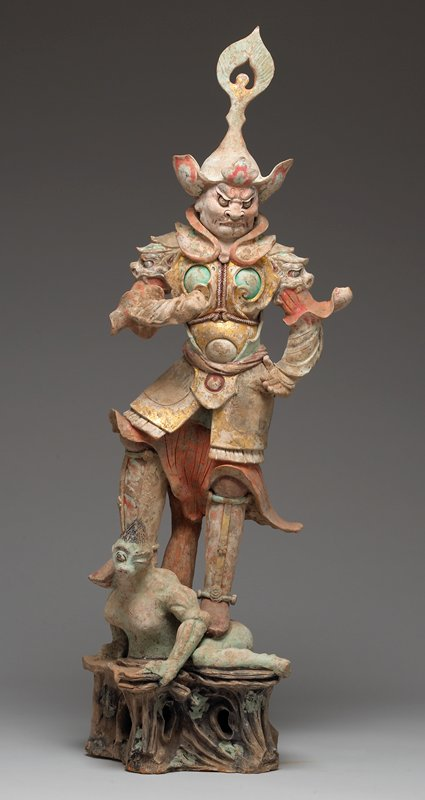 standing male figure wearing armor and tall hat, with moustache and pointed beard, biting lip; figure stands with both feet on a winking green-skinned demon with pig snout and breasts