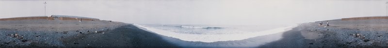 410 degree panoramic color photograph; surfers in distance at center; shore extending to right and left, covered in debris; several figures on shore at right and left; wall visible to right and left