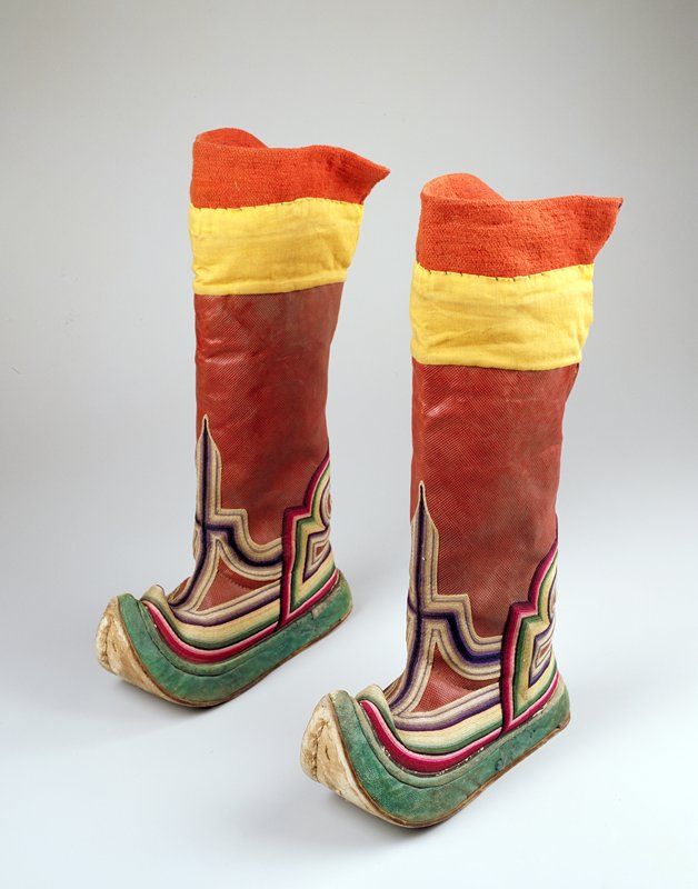 red leather with stamped hatching on leg; yellow and red fabric at top; applied multicolored braiding on foot; curled and pointed toe; green leather on edge of foot