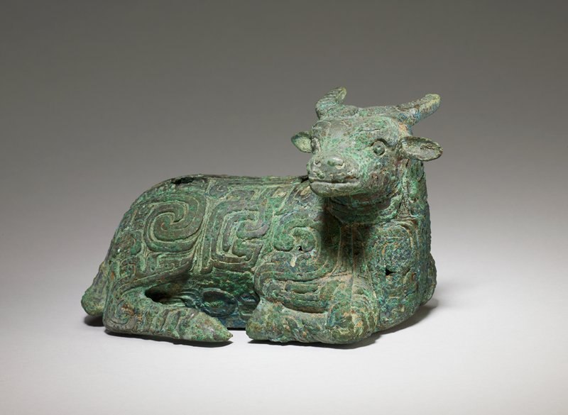 Ox (water buffalo), recumbent. The pose of this buffalo, with legs folded in under the body and head turned to the side, is typical of the northern nomad style and may be influenced by the Northern art. The decor is executed in broad bands in flat relief on a ground of spirals unobtrusive in comparison with the bold spirals emphasizing the shoulders and hind quarters of the beast. This decor of broad bands in spiral form is reminiscent, in its use of tufts, of earlier dragon decor. The slanting figures the hind legs and the chest recall those on the famous tigers in the Freer gallery. The holes in the back of the buffalo indicate that the piece had some practical use, as yet undetermined. Patina green