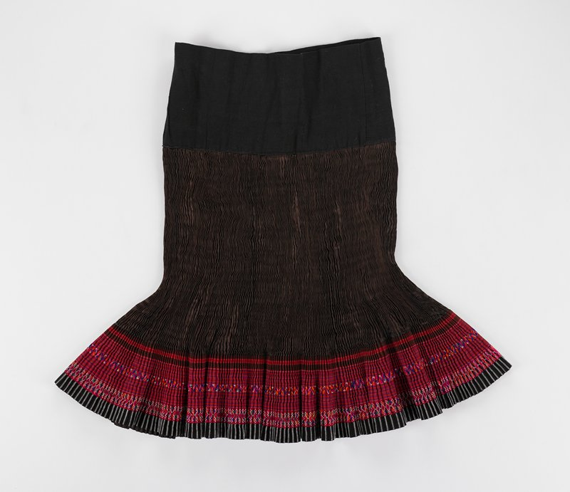 black waistband; brown silk body with tight pleats; predominately red and fuscha bands at hem of striped fabrics and geometric embroidery