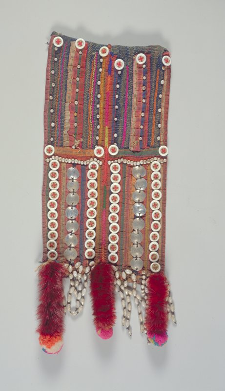 cloth panel with linear embroidery and applique; 4 vertical rows of buttons and 2 vertical rows of metal disks; 3 maroon-dyed monkey tails with multicolored pompons at ends; fringe of hanging beads between tails