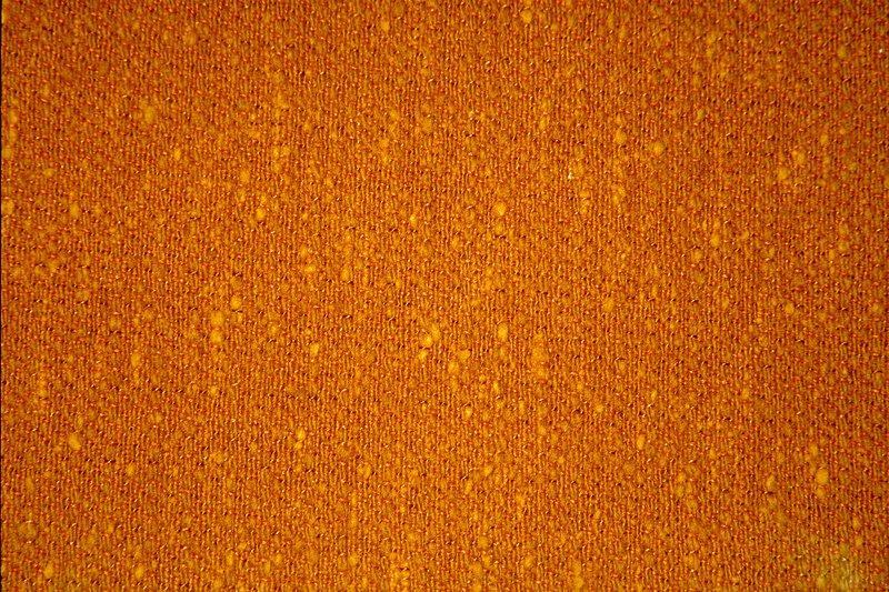 Plain weave. Thin gray warp. Thick weft, random shots using two weft threads. Mothproofed, scotchguard finish. Backed with acrylic latex. Plain weaqve. Thin orange warp. Thick weft, random shots using two weft threads. Mothproofed, scotchguard finish. Backed with acrylic latex. Brass
