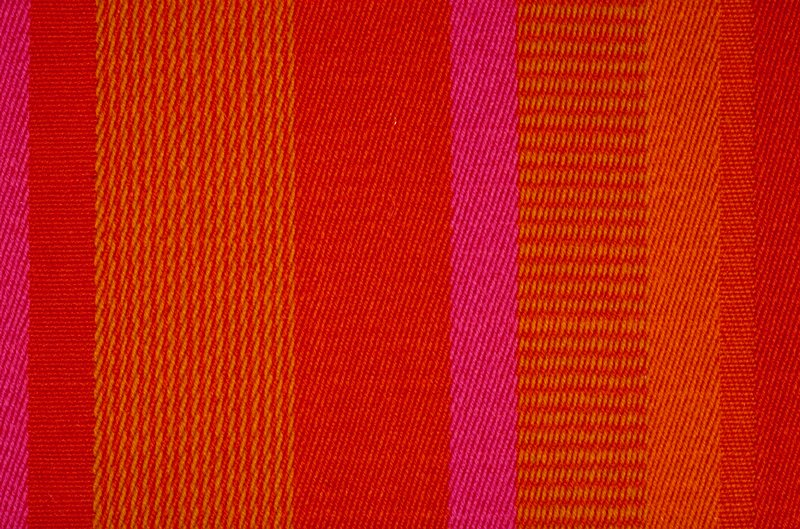 Multicolored warp and weft, stripes vary in width from 1 inch to 3.5 inches wide. No pattern repeat.. Twill weave. (Fuschia, orange, gold)