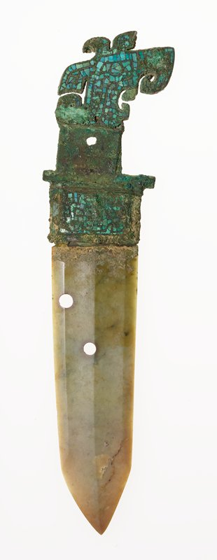 This weapon displays the assymetrically placed tang and the strongly crested head of a bird that was a ubiquitous motif in the bronze art of Yin time. The bird's head, and the socket fitted with a blade of jade, are inlaid with turquoise. The meaning of the two holes in the blade is obscure. Patina green.