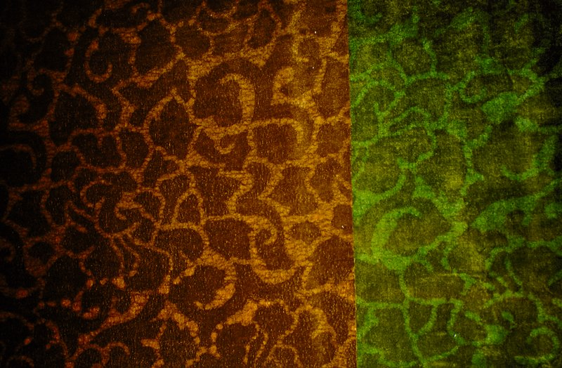 """Cotton velvet batik with scroll and floral design, forground in brown. Vertical pattern repeat at 16"""", horizontal repeat at 23 1/2. Green & olive. Right salvage includes handwritten numbers 13 and 14, 35"""" lengthwise. Jade"""
