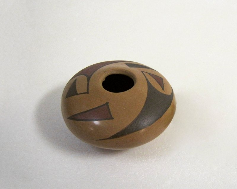 very small vessel with rounded bottom and very wide, steep shoulder; small mouth; tan body; decorated with geometric design (2 motifs) in red and brown