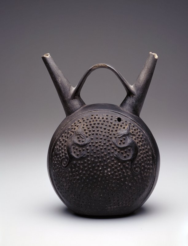 Black pot with double spout handle at top. In the side panels, two foxes in relief on a ground of all-over granular dots in relief.