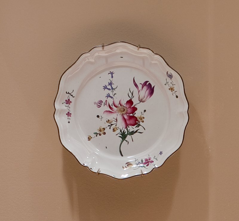 faience plate of a lobed hexagonal shape; typically edged with brown glaze; decorative ripple in the body of the plate. within the glazed ring; center is filled with a bouquet of the fleurs fines typical of Strasbourg