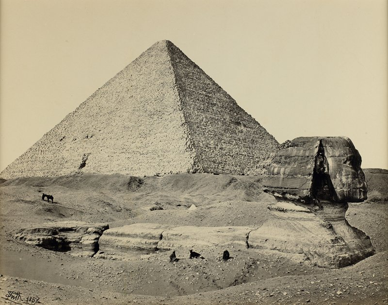 Sphinx, partially excavated, in foreground; three figures in front of Sphinx, pack animal behind; pyramid in background