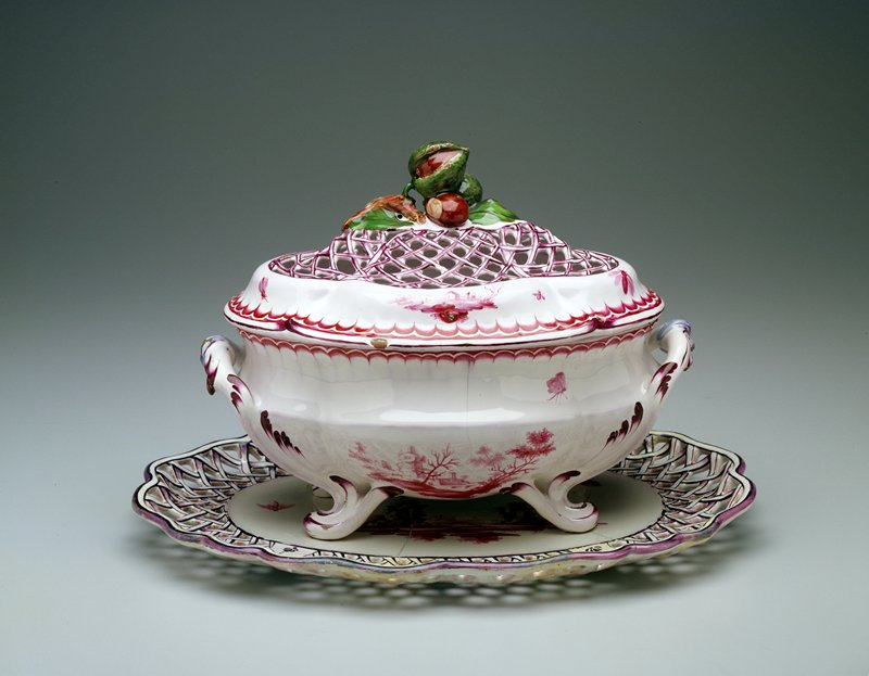 Covered two-handled faience tureen with pierced basket-weave stand; stand decorated with a landscape containing ruins and with insects painted in carmine; border outlined in purple; tureen has four sea-scroll feet; body decorated with landscape containing ruins and with more insects painted in carmine, and with acanthus motif in purple; border of tureen has painted scallop edge; pierced basket-weave lid, outlined in purple, with bunch of chestnuts painted in green and brown serving as finial