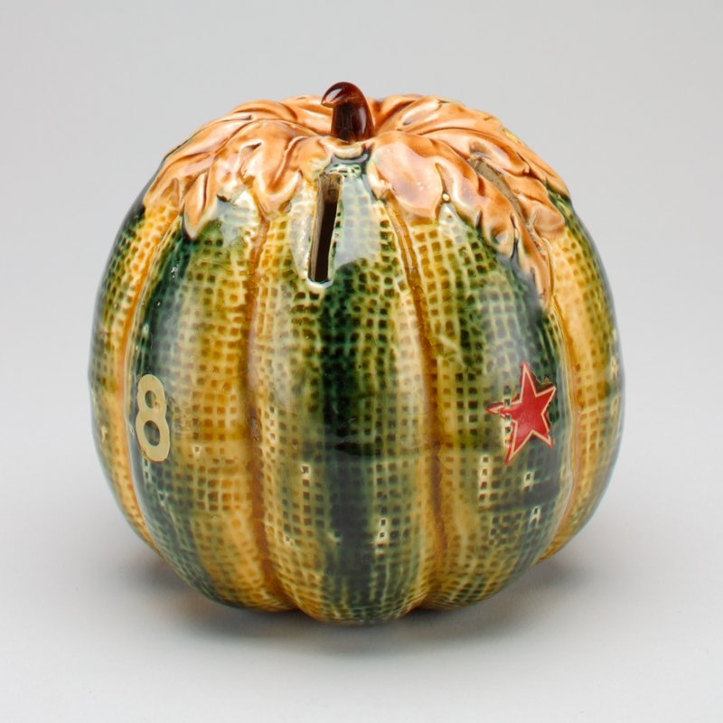 roundish ceramic green and gold squash with a brown leaf and stem on the top; highly textured, shiny surface; six coin slots in the sides;