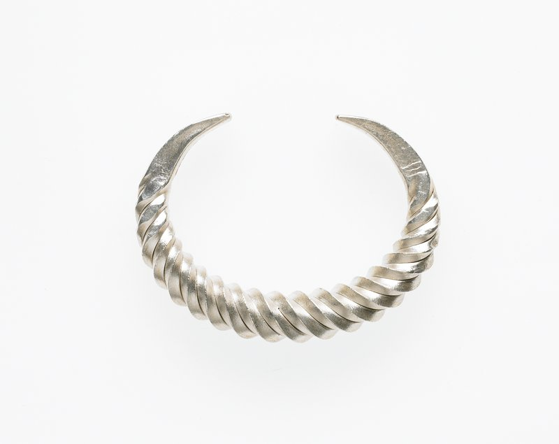 c-shaped; twisted design; tapering, flattened ends with incised arc design; silver patina