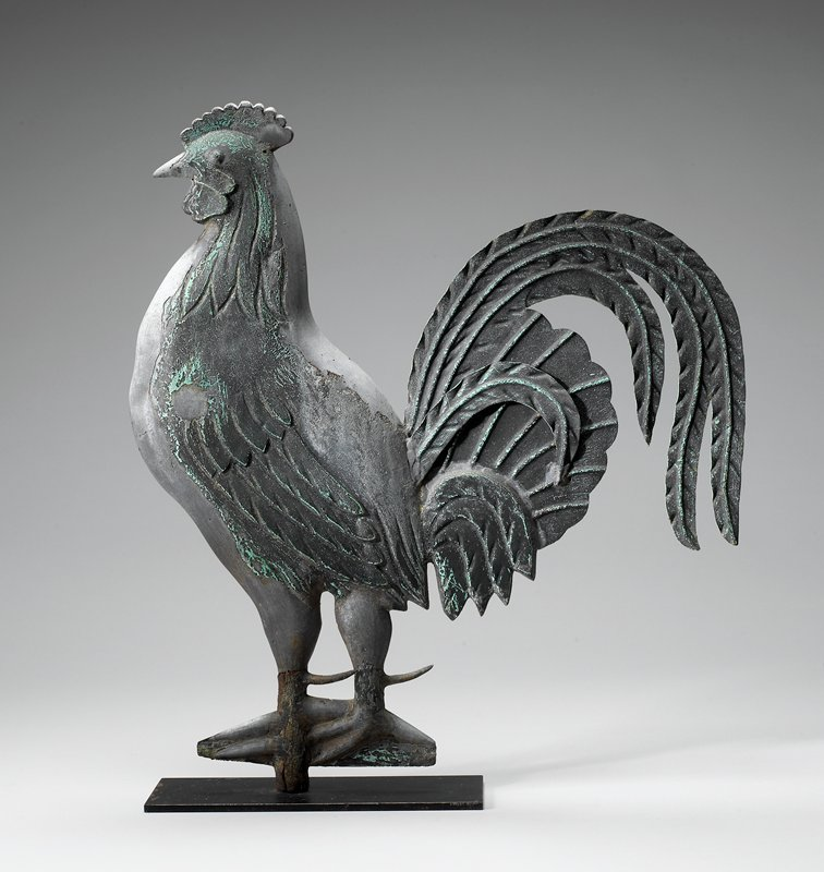 standing rooster; leaf-like delineated tail feathers; light-colored beak; green-black patina; stylized feet attached to metal sheet