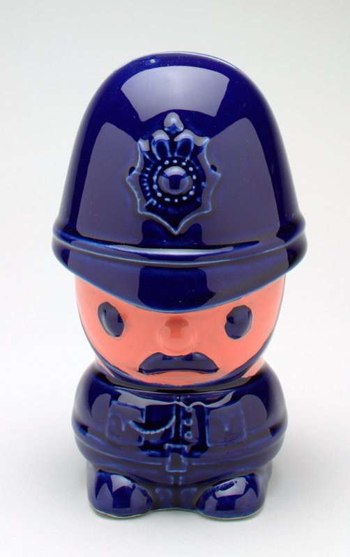 caricature of a London bobby in ceramic; blue hat with chip strap; blue uniform and shoes, blues eyes and moustache, pink face and hands; plastic cover on bottom with 'Made in England'; paper label on plastic with British flag insignia and 'British Made' printed on it