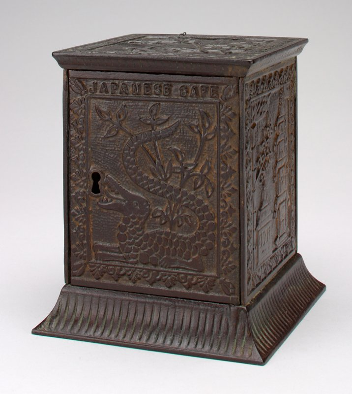 block shape with Japanese scenes on sides including dragon on door; pagoda, sailboat and lantern in garden; coin slot at top