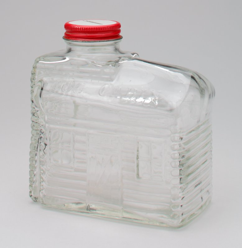 clear glass log cabin syrup bottle with coin slot cut into cover; on 2 sides of roof, in raised letters: 'Log Cabin'; red and white cap