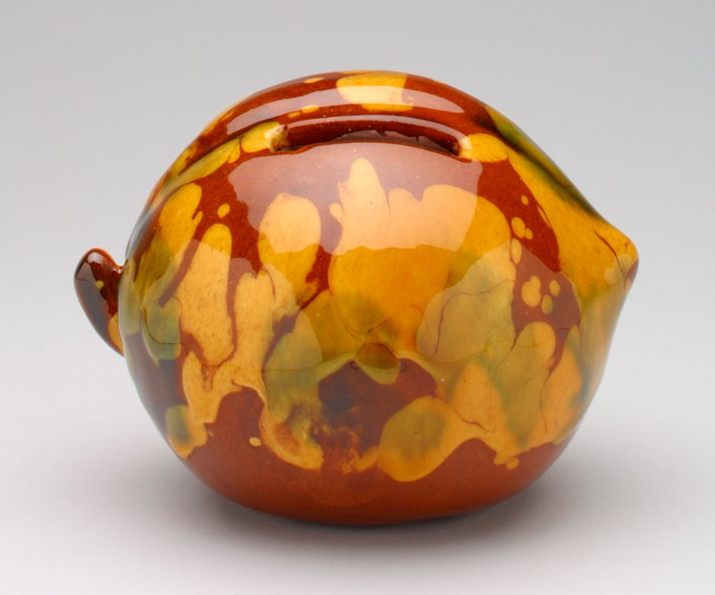 brown, green and yellow ceramic peach with shiny glaze; stem on one side; coin slot at top; letters incised on bottom