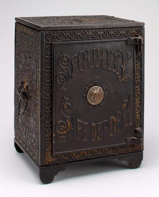 black rectangular box; elaborate scroll decorations overall; ring handles on sides attached to lion's heads; 2 drawers (b & c) inside with handles; coin slot on top
